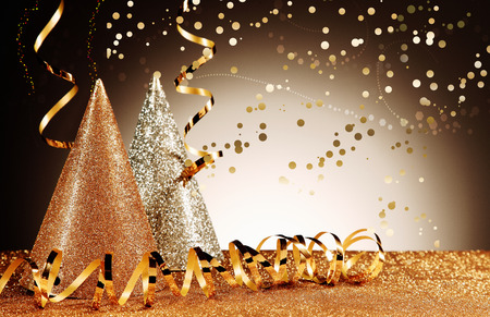 Celebration Concept - Close up Glittery Party Cone Hats with Shiny Streamers with Confetti Effect on Glittery Table in Front Gradient Brown Background. Banque d'images