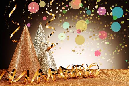 invitacion fiesta: Cierre de relucientes Carnaval Cono Sombreros y Gold Serpentinas con Efecto Confeti en el reluciente mesa en segundo plano frente Gradiente Marrón Foto de archivo