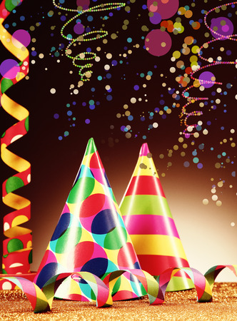 twirled: Festive Decoration Concept - Close up Colorful Party Hats and Streamers on Abstract Background