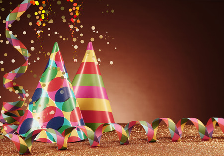 twirled: Close up Colorful Cone Party Hats and Paper Streamers on Table with Particles, Styled with Confetti Effect, on Gradient Brown Background. Stock Photo