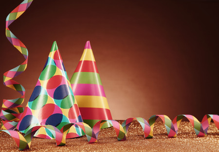 merrymaking: Close up Party Carnival Hats with Different Designs and Paper Streamers on Top of the Table, with Particles, in front Gradient Brown Background.