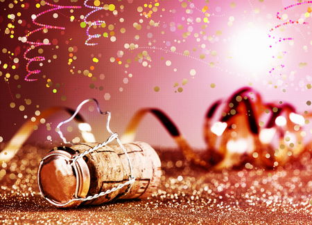 festive occasions: Close up Festive Champagne Cork in Metal Cage with Paper Streamers on Table with Particles. Styled with Glitters and Confetti Effect on Gradient Pink Background. Stock Photo