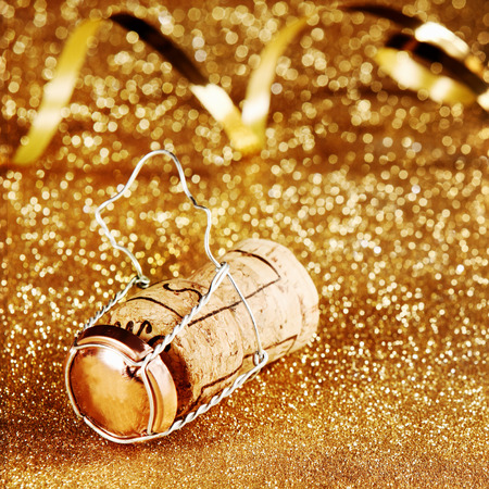 twirled: Festive Decoration Concept - Close up Wooden Wine Cork with Cage on Golden Particles with Paper Streamers.