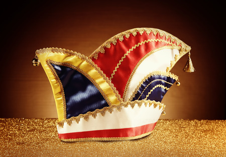 Close up Attractive Carnival Jester Hat on Glittery Platform in Front Gradient Brown Background. photo