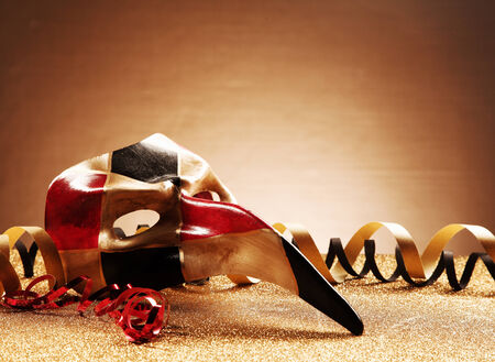 emphasizing: Close up Venetian Masquerade Mask with Streamers on Glittery Table In front Gradient Brown Background. Emphasizing Copy Space.