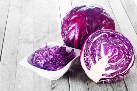 クローズ アップ細切り、スライス、全体の紫キャベツ野菜木製のテーブルの上に