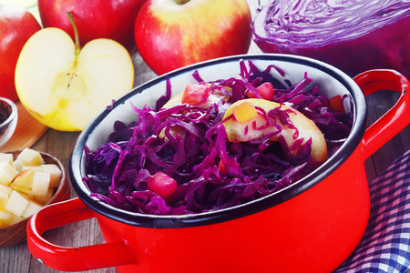 red cabbage: Close up Appetizing Shredded Purple Cabbage with Apple Slices Salads on a Red Pot, Placed on Wooden Table with Fresh Ingredients.