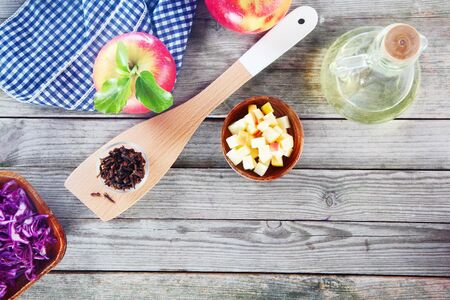 emphasizing: Aerial Shot of Salad Recipe Ingredients on Top of Wooden Table, Emphasizing Apples, Cabbage and Vinegar with Napkin and Wooden Ladle. Stock Photo