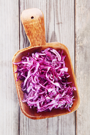 red cabbage: Close up Healthy Fresh Shredded Purple Cabbage on Wooden Bowl on Top of Wooden Table. Stock Photo