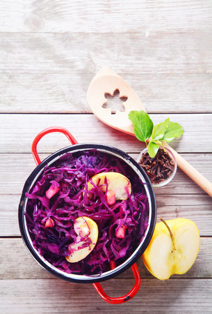 red cabbage: Close up Gourmet Healthy Red Cabbage and Apple Salad on Pot, Placed on Wooden table with Slice of Apple, Spices and Wooden Ladle.