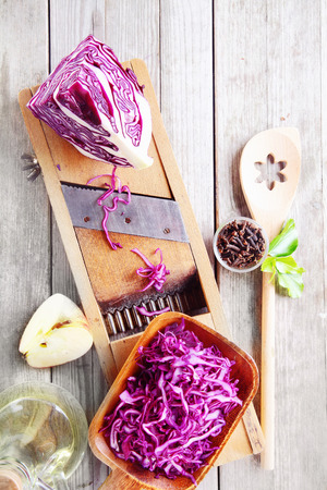 slicing: Close up Fresh Purple Cabbage and Apple Salad Ingredients on Wooden Table with Shredder and Wooden Ladle. Stock Photo