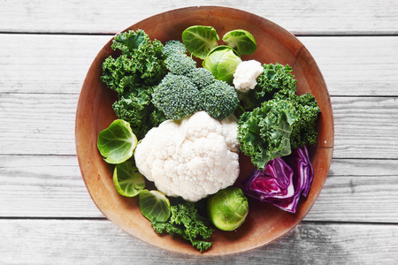 Close up Healthy Fresh Salad Ingredients with Broccoli, Cauliflower, Purple Cabbage and Brussels Sprout on Wooden Bowl, Placed on Wooden Table. Stock Photo