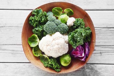 coliflor: Close up sanos ingredientes de la ensalada fresca con brócoli, coliflor, col púrpura y las coles de Bruselas en cuenco de madera, colocada sobre la mesa de madera.