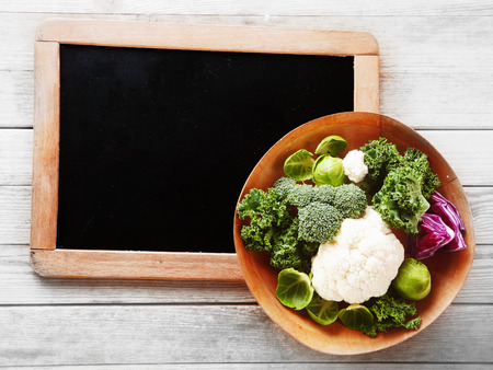 emphasizing: Close up Fresh Salad Ingredients, with Broccoli, Cabbage and Cauliflower on Wooden Bowl, Placed on Small Chalkboard Corner on Top of Wooden Table. Emphasizing Copy Space. Stock Photo