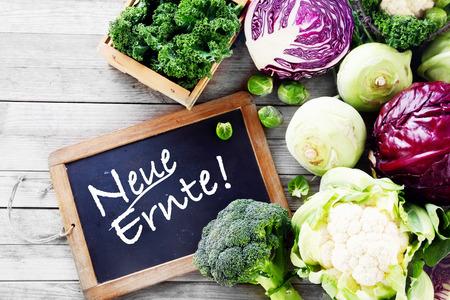 legumes: Close up nouvellement r�colte de chou rouge, chou-fleur, brocoli et choux de Bruxelles sur la table en bois avec Black Chalkboard Signage
