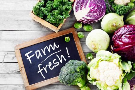 クローズ アップ サラダ黒黒板の看板を持つ木製テーブルの上の農場からの新鮮な野菜 写真素材