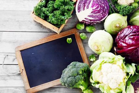 クローズ アップ黒黒板を持つ木製テーブルに農場から新鮮な野菜のサラダ。コピー スペースを強調します。