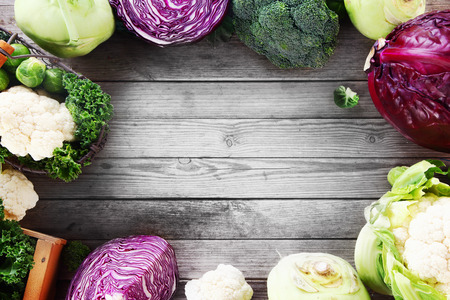 Frame of various brassica cabbage family varieties with cauliflower, kohlrabi, kale, cabbage and brussels sprouts over a rustic wooden background with copyspace