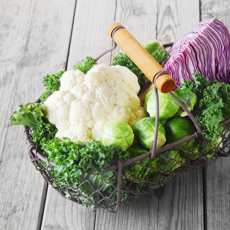 Wire basket of farm fresh cruciferous vegetables with a cauliflower, red cabbage, brussels sprouts and leafy green kale on rustic grey wooden boards