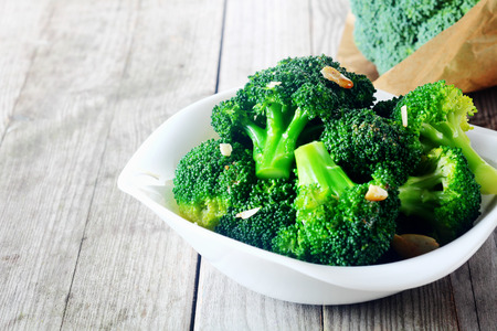 Close up Flavored Steamed Fresh Broccoli on White Plate, Served on Top of Wooden Table.
