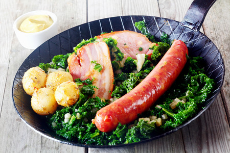 cooked sausage: Close up Gourmet German Cuisine on Frying Pan, Emphasizing Cooked Sausage, Meat and Potatoes on Kale Veggies, with Mustard on Side Stock Photo
