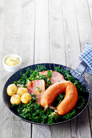 Close up Healthy German Recipe on a Frying Pan with Mustard Sauce on Side, Placed on Wooden Table. photo
