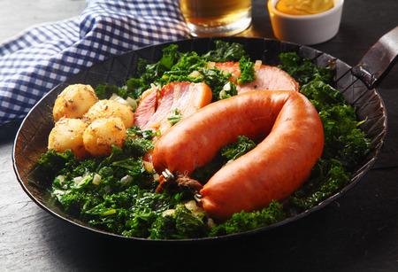 german sausage: Close up Gourmet German Sausage, Smoked Pork and Potatoes on Top of Green Veggies, Served on a Frying Pan.