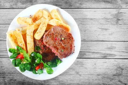 carne asada: Cierre de tiro a�reo de carne a la parrilla sabrosa con las patatas fritas y las hierbas en la placa blanca encima de la tabla de madera.