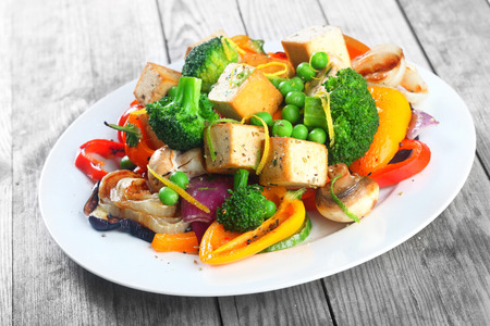 quick snack: Healthy vegetarian cuisine with a tofu salad with colorful roast vegetables including sweet peppers, onion and mushrooms, peas and broccoli