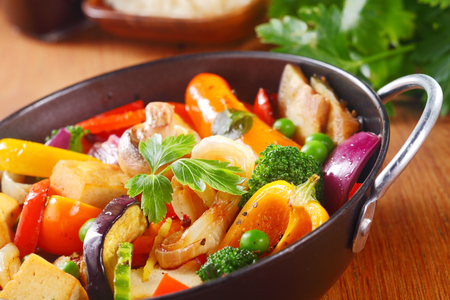 ovenbaked: Close up Healthy Cooked Main Dish with Veggies and Spices on a Black Pan with Herbs, Placed on Wooden Table.