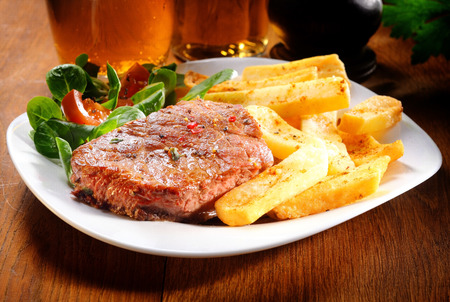 rump steak: Gourmet Healthy Grilled Beef and Potato French Fries on White Plate with Herbs and Veggies. Placed on Wooden Table.