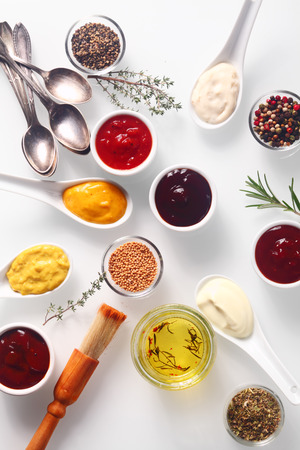 Spicy Close up Rubs and Marinades on White Table with Spoons and Brush. Imagens - 36400404