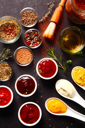 Close up Fresh Various Spices and Sauces on the Black slate kitchen Table photo
