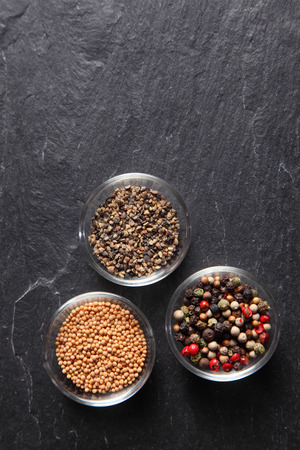 flavoring: Close up Assorted Seed Type Spices on Containers Placed on slate background, Emphasizing Copy Space. Stock Photo