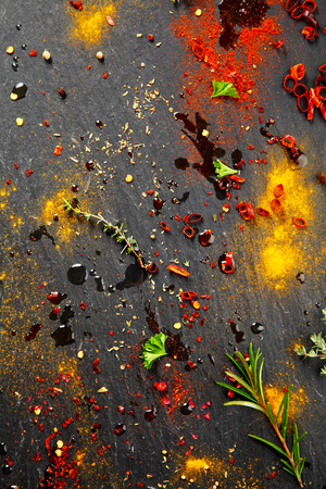 marinate: Close up Messy Black Table with Assorted Colored Rub and Marinade Spices