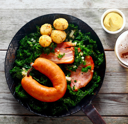 brassica: Close up Aerial Shot of Gourmet German Recipe with Sausage, Pork and Potatoes with Kale on a Frying Pan. Served on Wooden Table with Mustard Sauce and Beer on the Side. Stock Photo