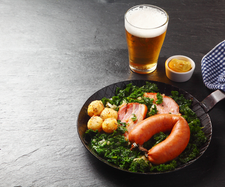 Close up Appetizing German Recipe with Sausage, Pork Meat, and Potatoes on Green Vegetables, Served on a Frying Pan with Beer and Sauce on the Side. Dine in Black Wooden Table.