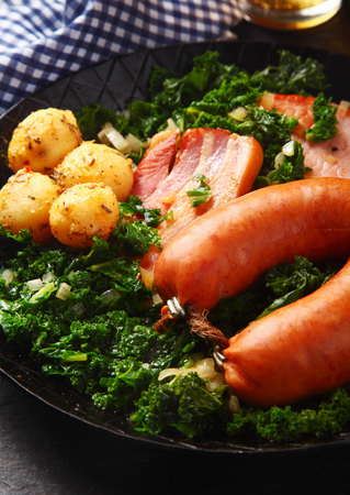 emphasizing: Close up Tasty German Recipe on a Frying Pan, Emphasizing Cooked Sausage, Pork Meat and Potatoes on Green Vegetables. Stock Photo