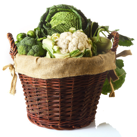 Close up Fresh Farm Vegetables in a Basket, Emphasizing Cauliflower, Brussels Sprouts, Broccoli and Cabbage. Isolated on White Background.
