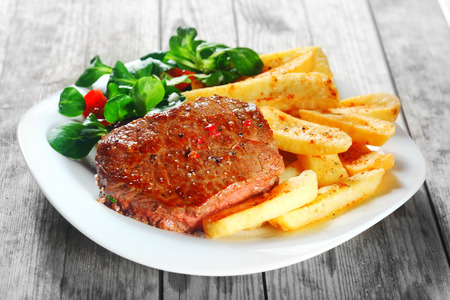 frites: Close up Gourmet Flavored Grilled Meat with French Fries on White Plate, Placed on Wooden Table.