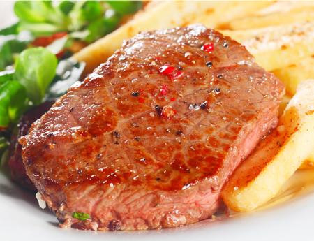 carne asada: Cierre de Gourmet jugosa carne a la parrilla en plato blanco con patatas fritas.