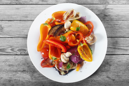 vegan food: Close up Aerial Shot of Appetizing Healthy Recipe with Mushrooms and Spices on White Plate. Placed on Wooden Table. Stock Photo