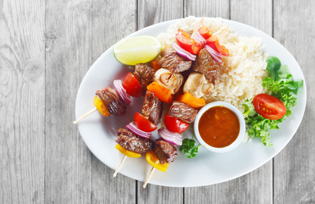 quick snack: Aerial Shot of Gourmet Meat and Spices Kebabs on White Plate with Sauce, Rice and Fresh Veggies on Wooden Table.