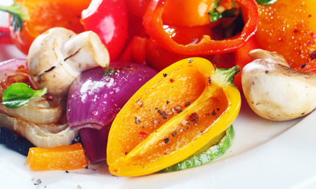 ovenbaked: Assorted colorful healthy plate of roast or grilled vegetables with bell peppers, mushrooms, onions and herbs for a tasty vegetarian meal or accompaniment Stock Photo