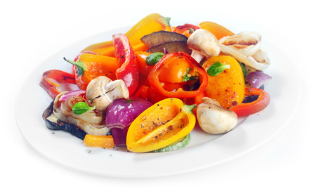 Succulent roasted vegetables side dish or vegetarian meal with sweet peppers, mushrooms onions and herbs on a plate over white
