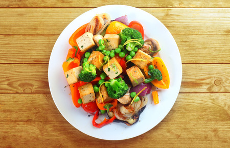 Overhead view of a plate of healthy grilled roast vegetables with tofu, or soybean curd, on a wooden table
