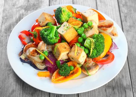 グルメ健康的なメイン料理豆腐、ブロッコリー、きのこ、豆、スパイスとホワイト プレート上を閉じます。木製のテーブルで提供しています