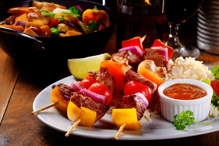 Main Entree Concept - Close up Appetizing Kebabs on Rice with Tomato Sauce, Served on White Plate on Top of Wooden Table. Stock Photo