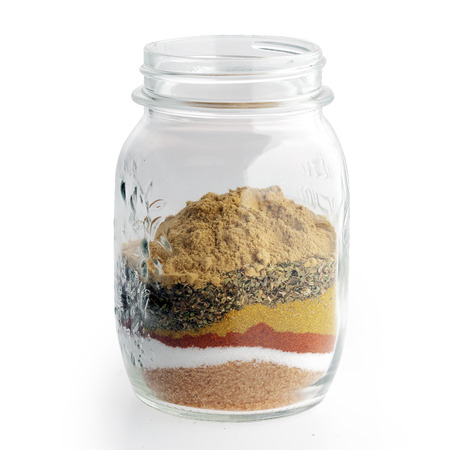 Close up Rubs, Spice Blends, Marinades, and Brines on a Glass Jar Isolated on White Background. photo