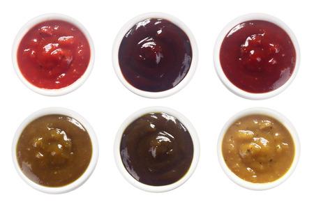 salsa de tomate: Cierre de tiro aéreo de Surtido de salsas picantes en platillos, aislado en blanco.